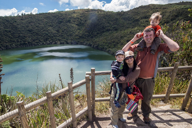 A young family smiles while standing on an over look over a crater lake surrounded by jungle as they search for the lost city of gold in Guatavita Colombia with kids
