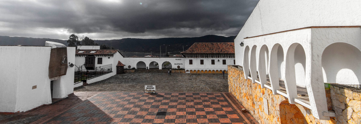 Storm clouds roll over bring white spanish style buildings with red roofs - Legend of El Dorado in Colombia
