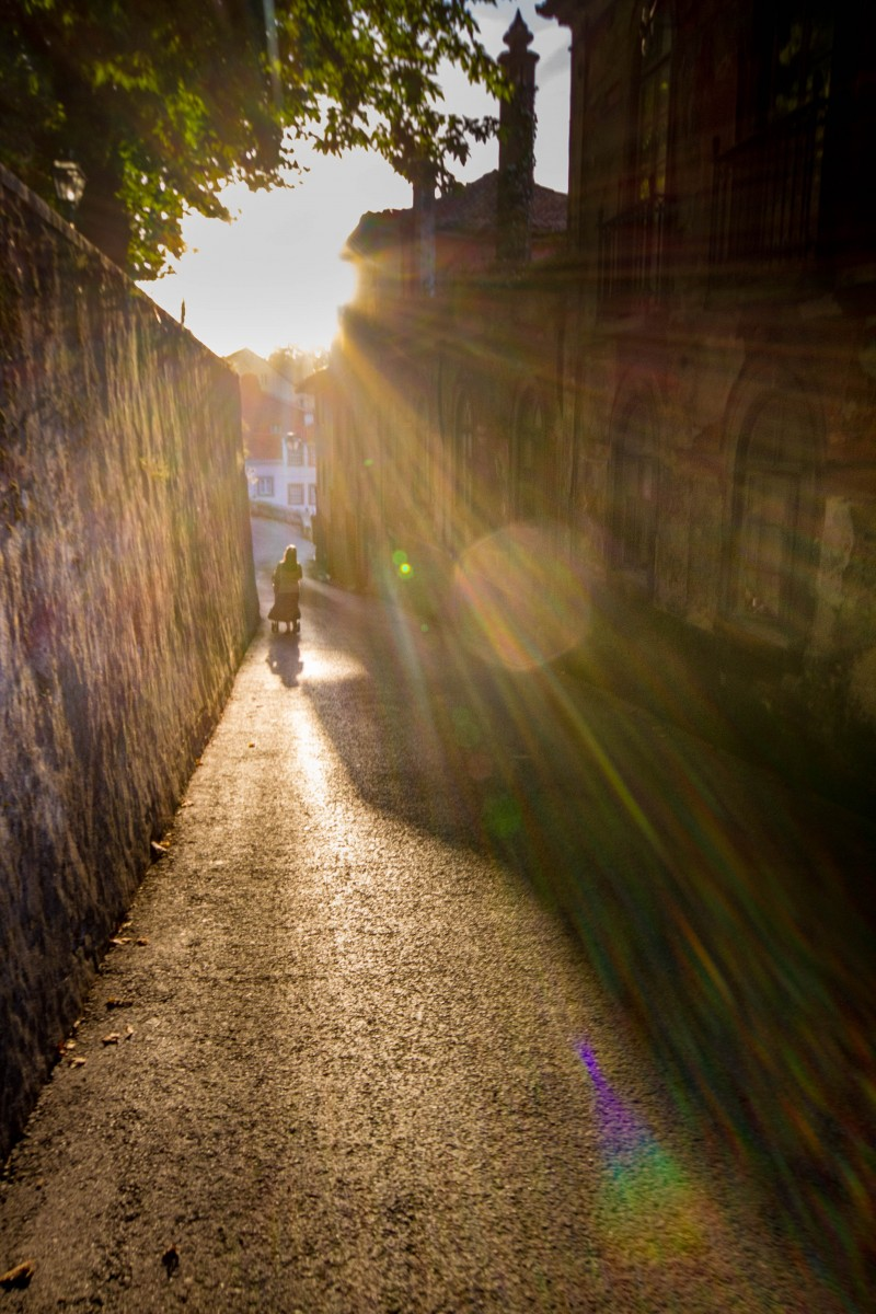 A woman pushes a baby stroller down a narrow cobblestone street while the suns rays explode around her - Sintra, Portugal