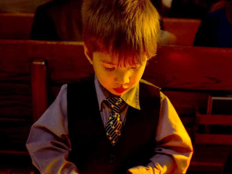 A young boy in a vest and tie sitting in church