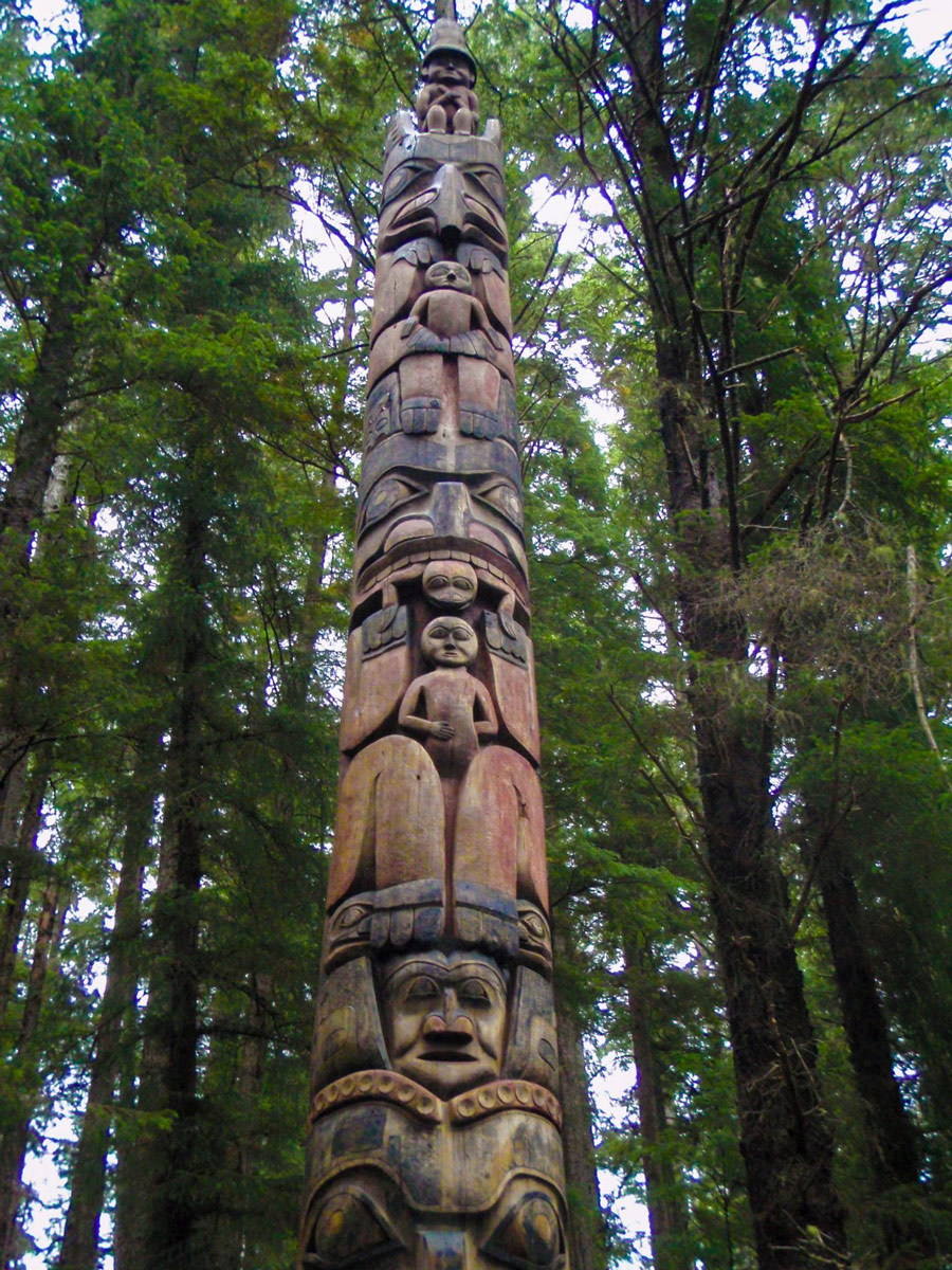 A lone totem pole amidst tress in Sitka's National Historical Park.