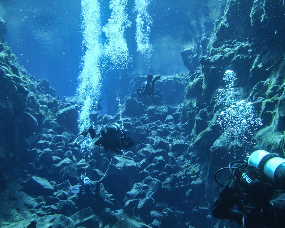 SCUBA divers in the Silfra Crack in Iceland