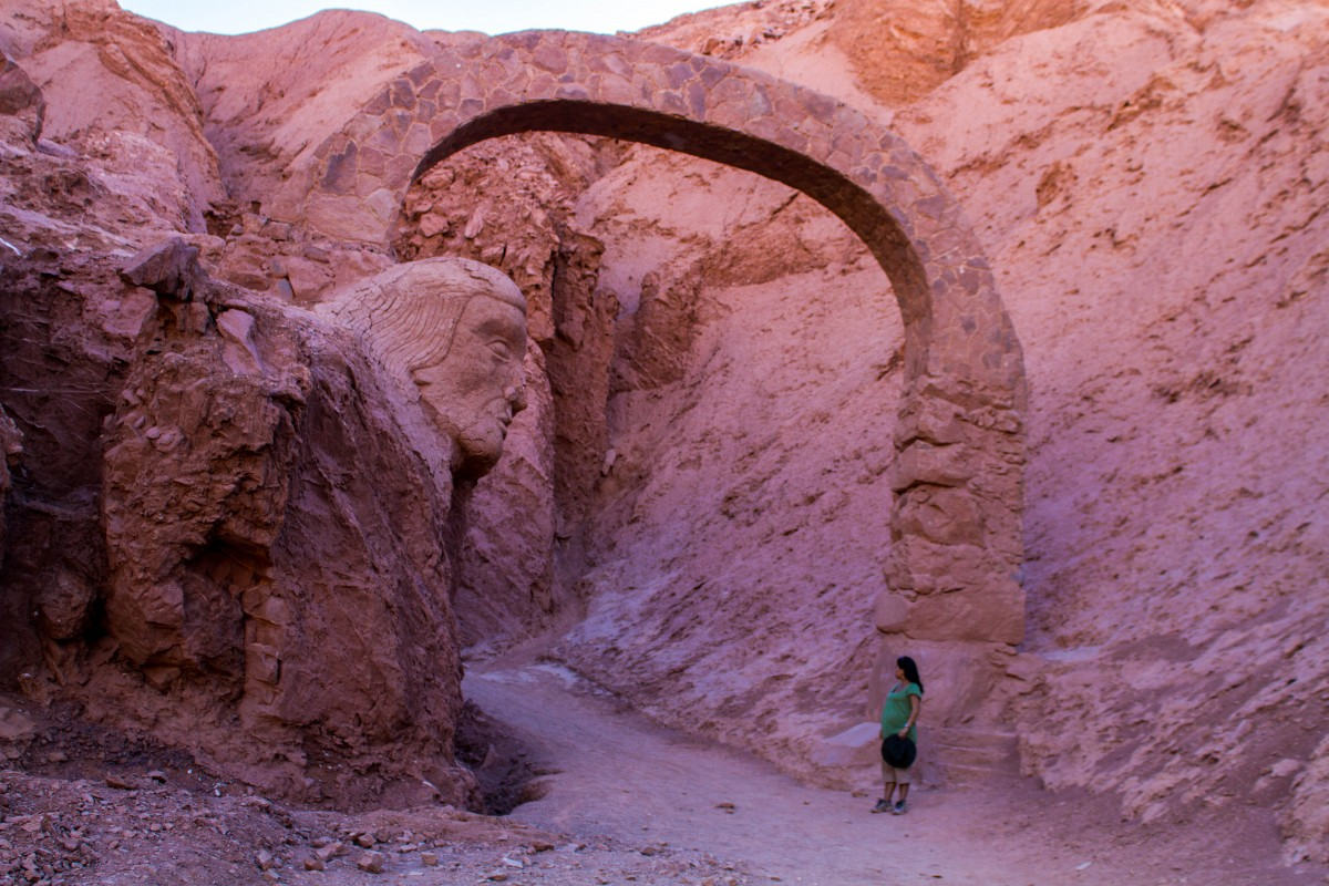 A pregnant woman stands near a tall stone arch with a carving of an indigenous person