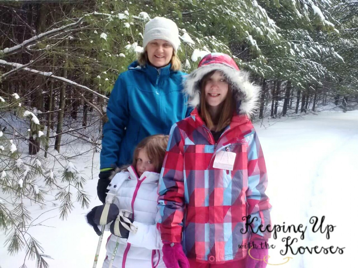 Smiling Mom and daughters in snow gear - Skiing North Michigan