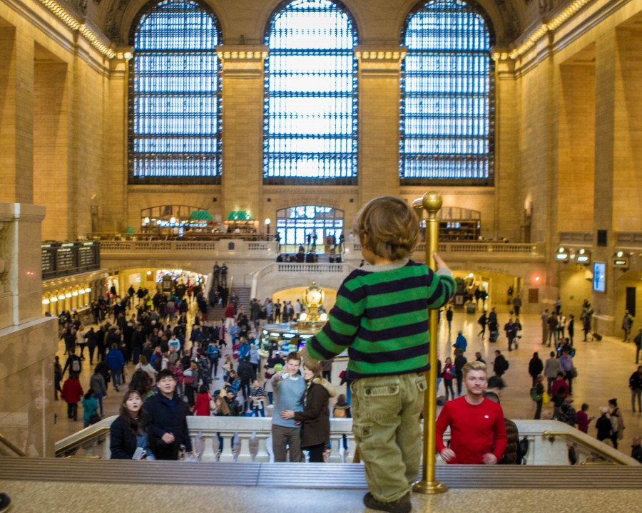 A toddler stands at the top of the stairs looking out over the inside of Grand Central Station in New York City during a city sightseeing new york