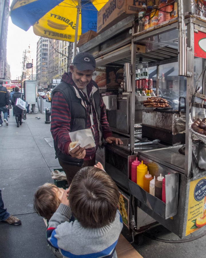 A smiling hot dog vendor hands the boys a warm pretzel on the streets of New York
