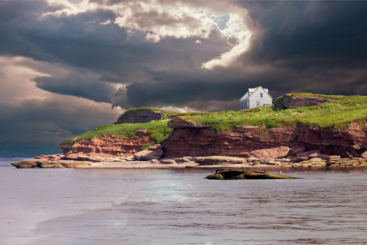 A lone farm house sits on the edge of a cliff against a moody sky near Perce, Quebec on the Gaspe Peninsula