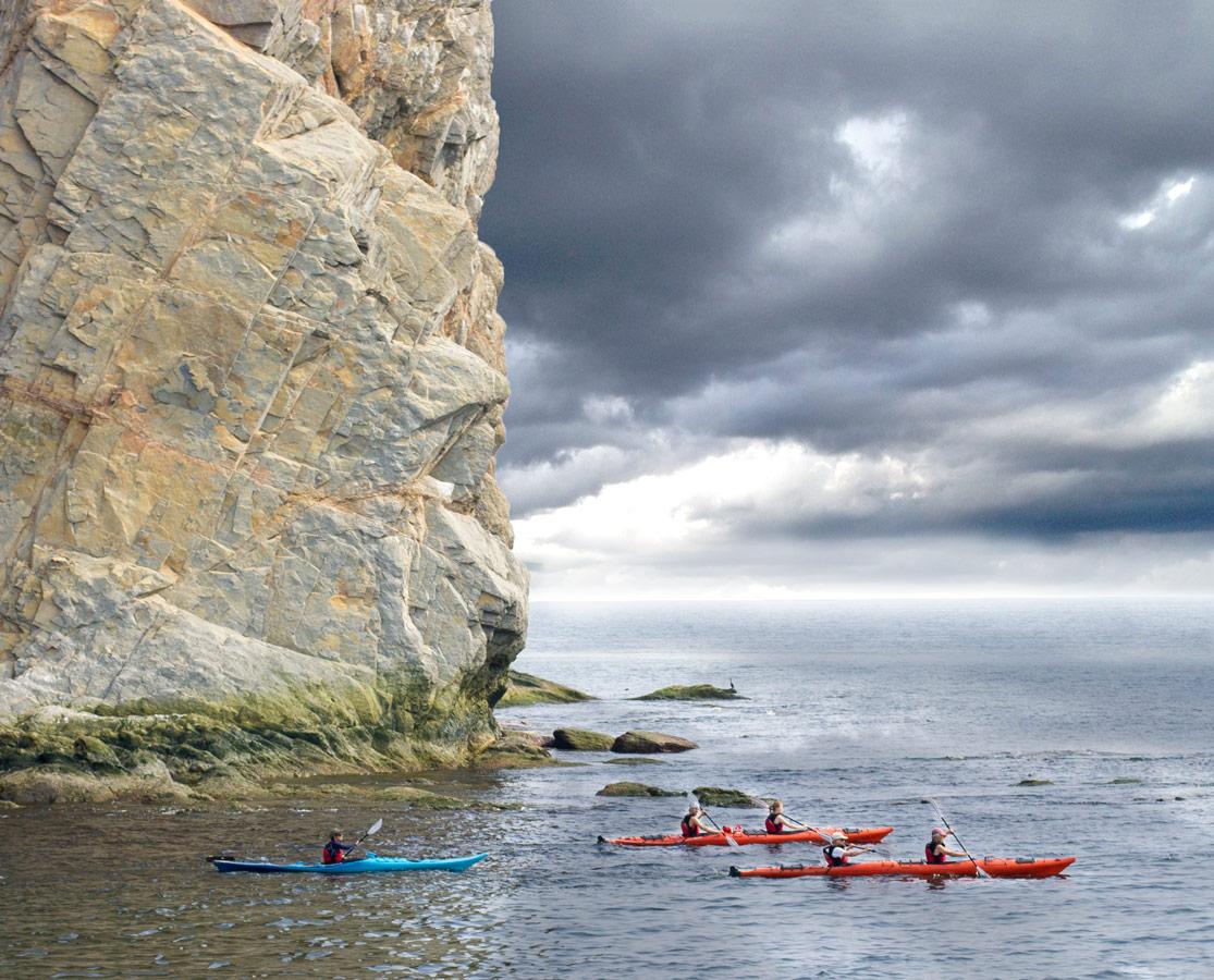 Kayakers explore the area around Perce Rock near Bonaventure Island on the Gaspe Peninsula of Quebec