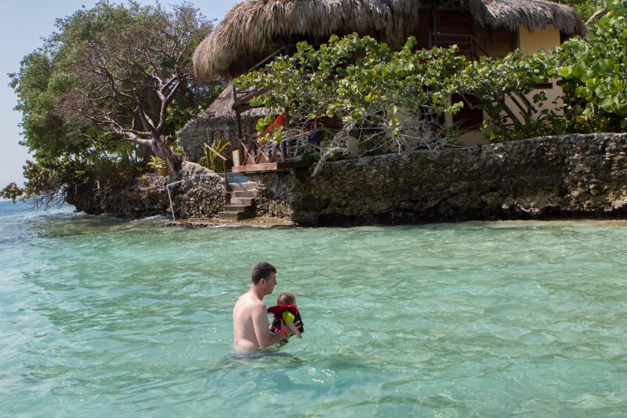 Man holds baby in the waters off of Pirate Island.