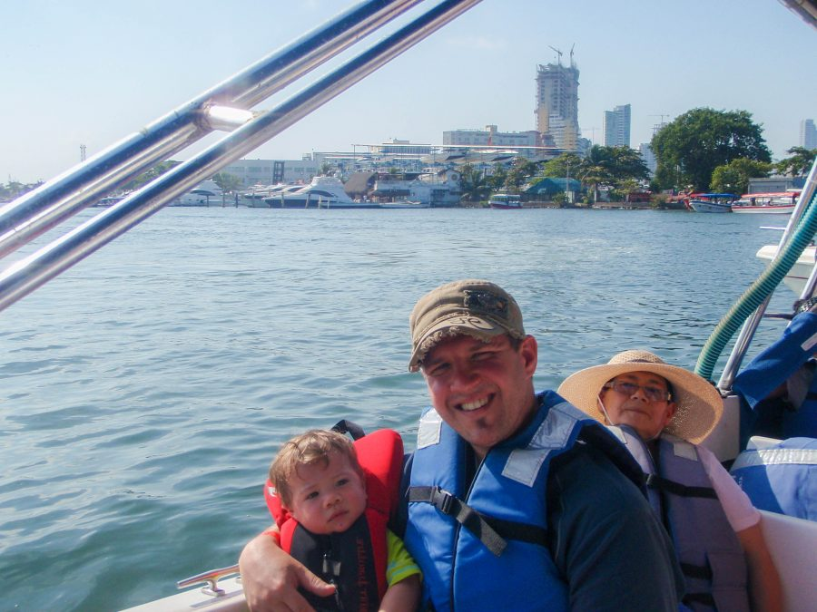 Father holds son on his lap on boat to Pirate Island.