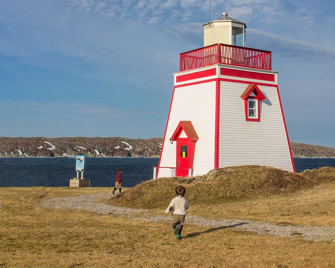 Children run toward Fox Point Lighthouse in St Anthony Newfoundland