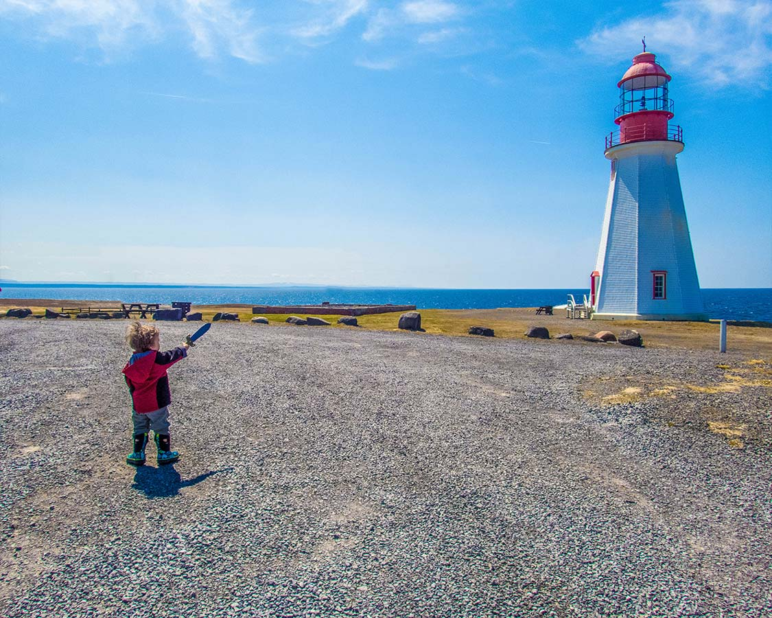Young boy with a toy sword points at a Lighthouse in Newfoundland
