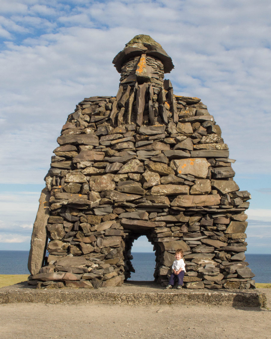 A young boy sits on the toe of a giant vikings sculpture on the coast of Iceland - An Epic 14 Day Iceland Itinerary