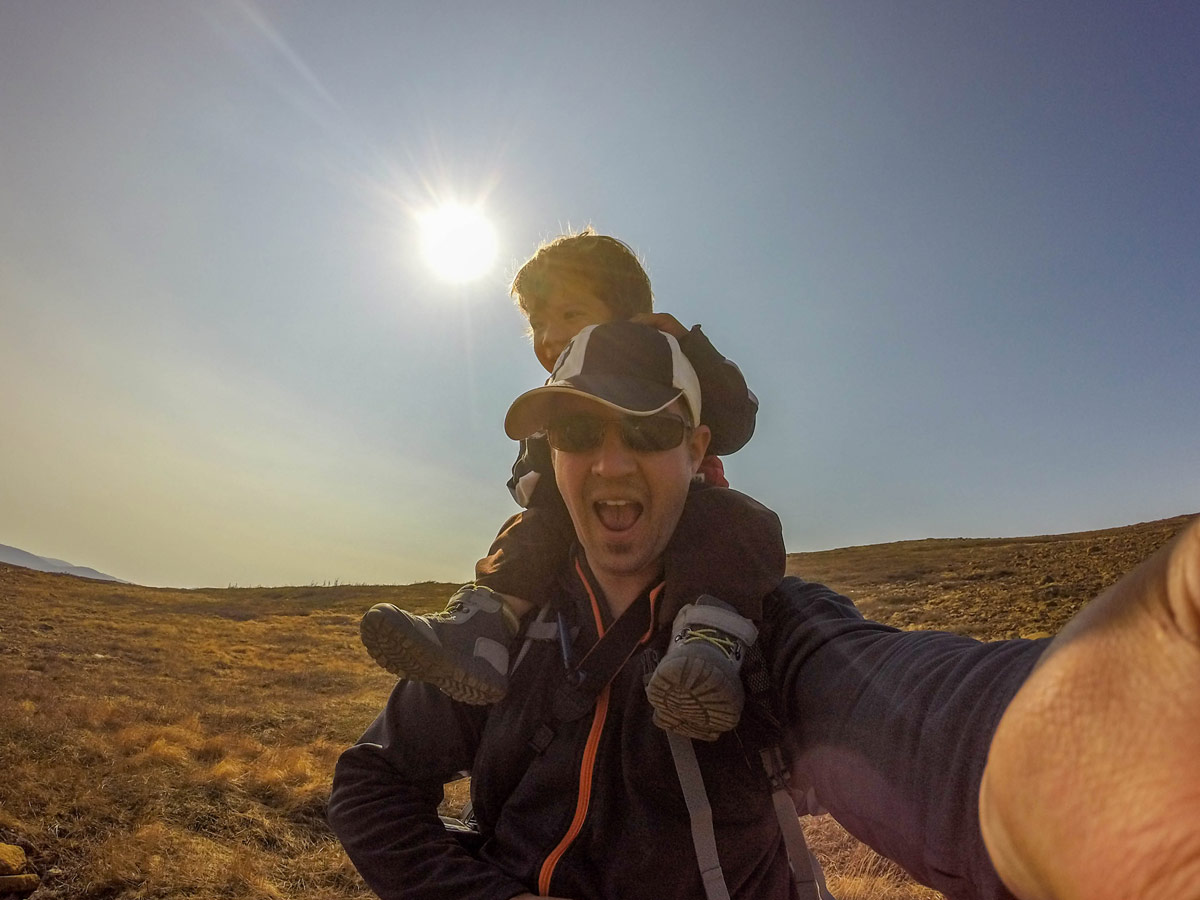 A father smile at the camera while giving a piggy back to a toddler on a hike through Gros Morne National Park - Hiking Green Gardens in Gros Morne National Park
