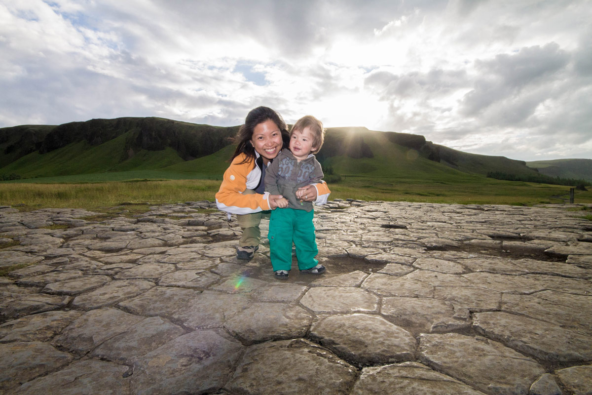 A mother and young boy smile on honeycomb shaped rocks - An Epic 14 Day Iceland for kids Itinerary
