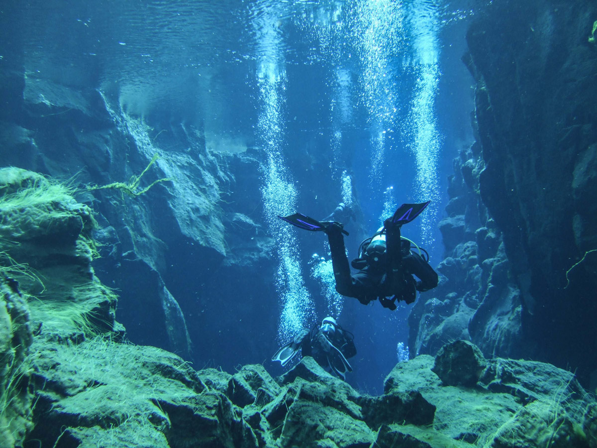 two scuba divers in clear waters near algae covered cliffs - An Epic 14 Day Iceland Itinerary