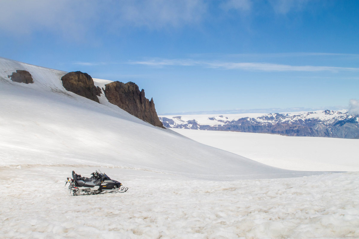 Snowmobiles sit near a rocky cliff on on an Icelandic glacier - An Epic 14 Day Iceland Itinerary