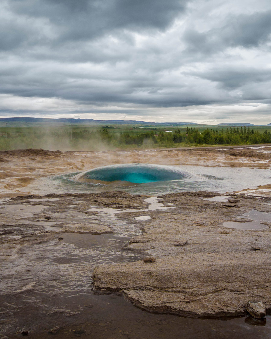 A blue bubble forms right before an eruption of a geyser - An Epic 14 Day Iceland Itinerary