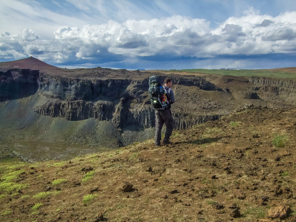 a man carrying a child in a kid-carrier hikes along a canyon rim - An Epic 14 Day Iceland Itinerary