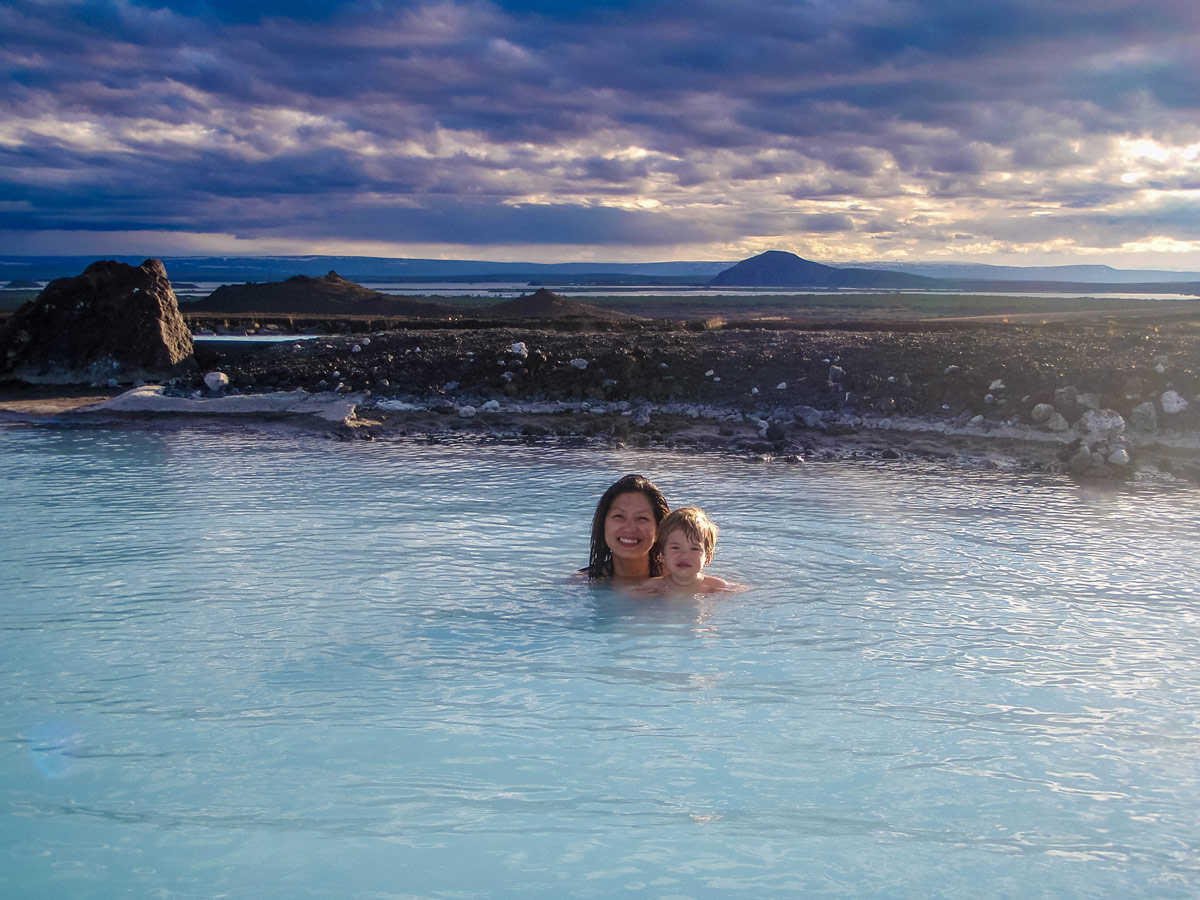 A woman and young son bath in the hot springs with rocky planes behind them - An Epic 14 Day Iceland Itinerary