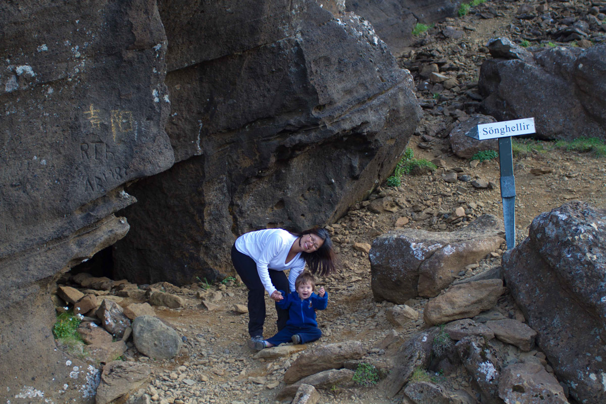 A woman and a young boy smile outside a cave in Iceland - An Epic 14 Day Iceland Itinerary