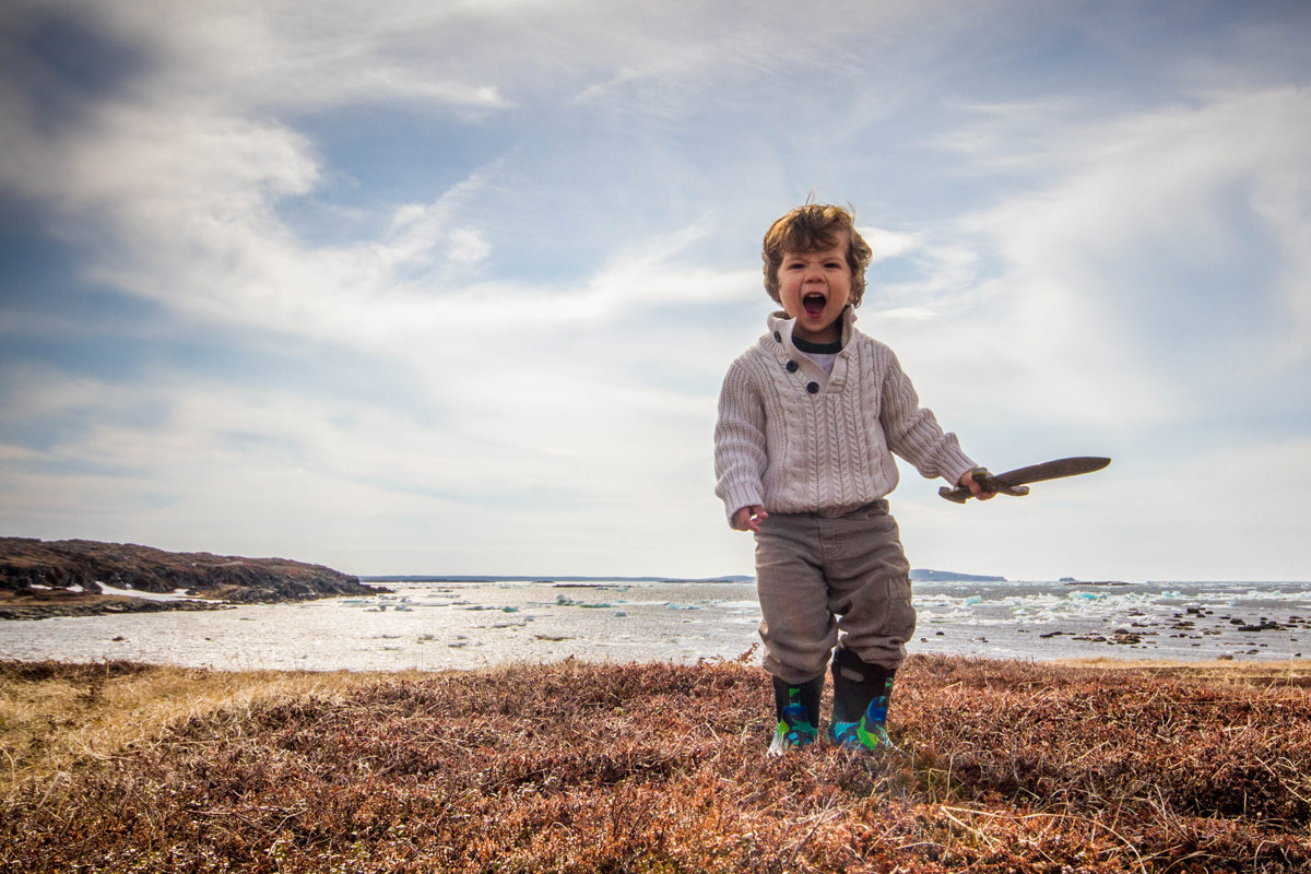 A young boy in a whole sweater, carrying a toy sword screams fiercely at a Viking village - Newfoundland Viking Trail