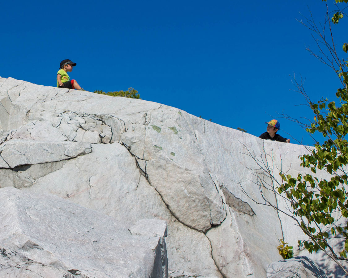 Two young boys sit on a white rock against a blue sky - Hiking the Crack in Killarney with Kids