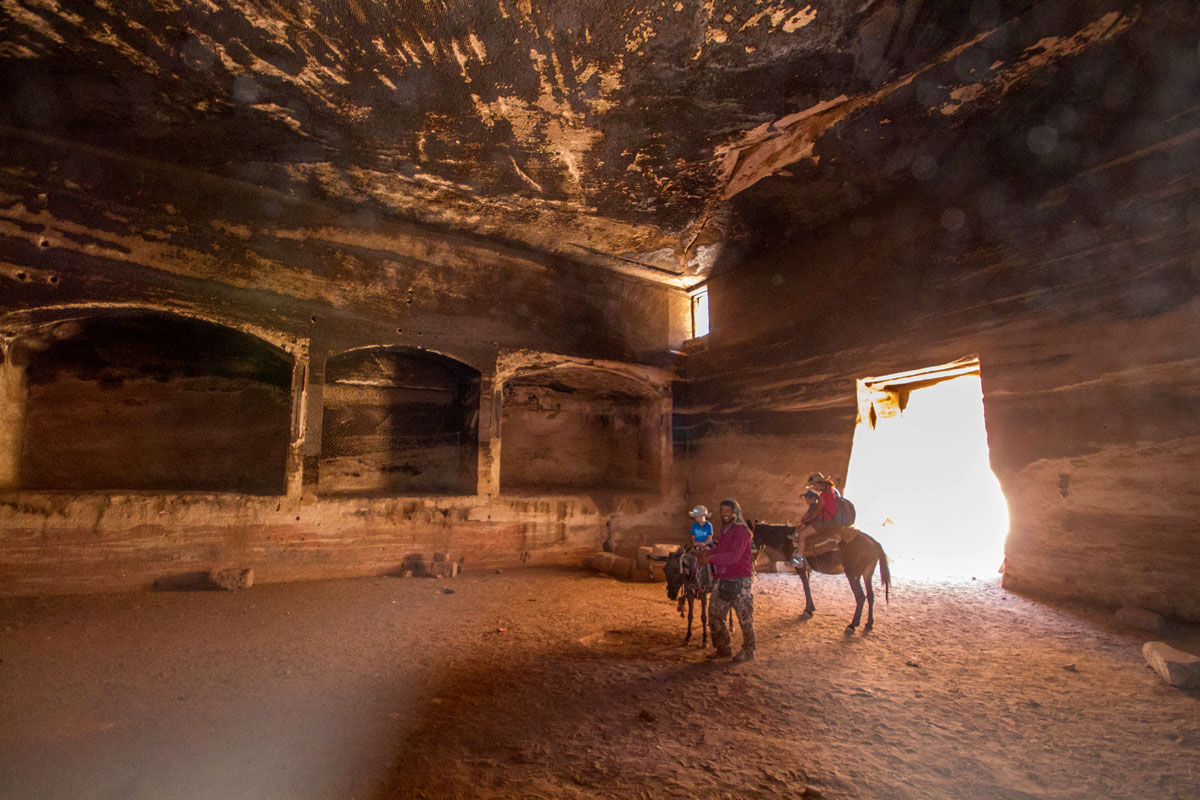 A guide and a young family ride horses inside a cave in Petra Jordan - Caves you can visit with kids