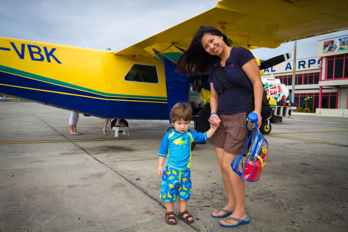A woman an toddler son smile while boarding a small yellow airplane - Swimming with Turtles in the Tobago Cays