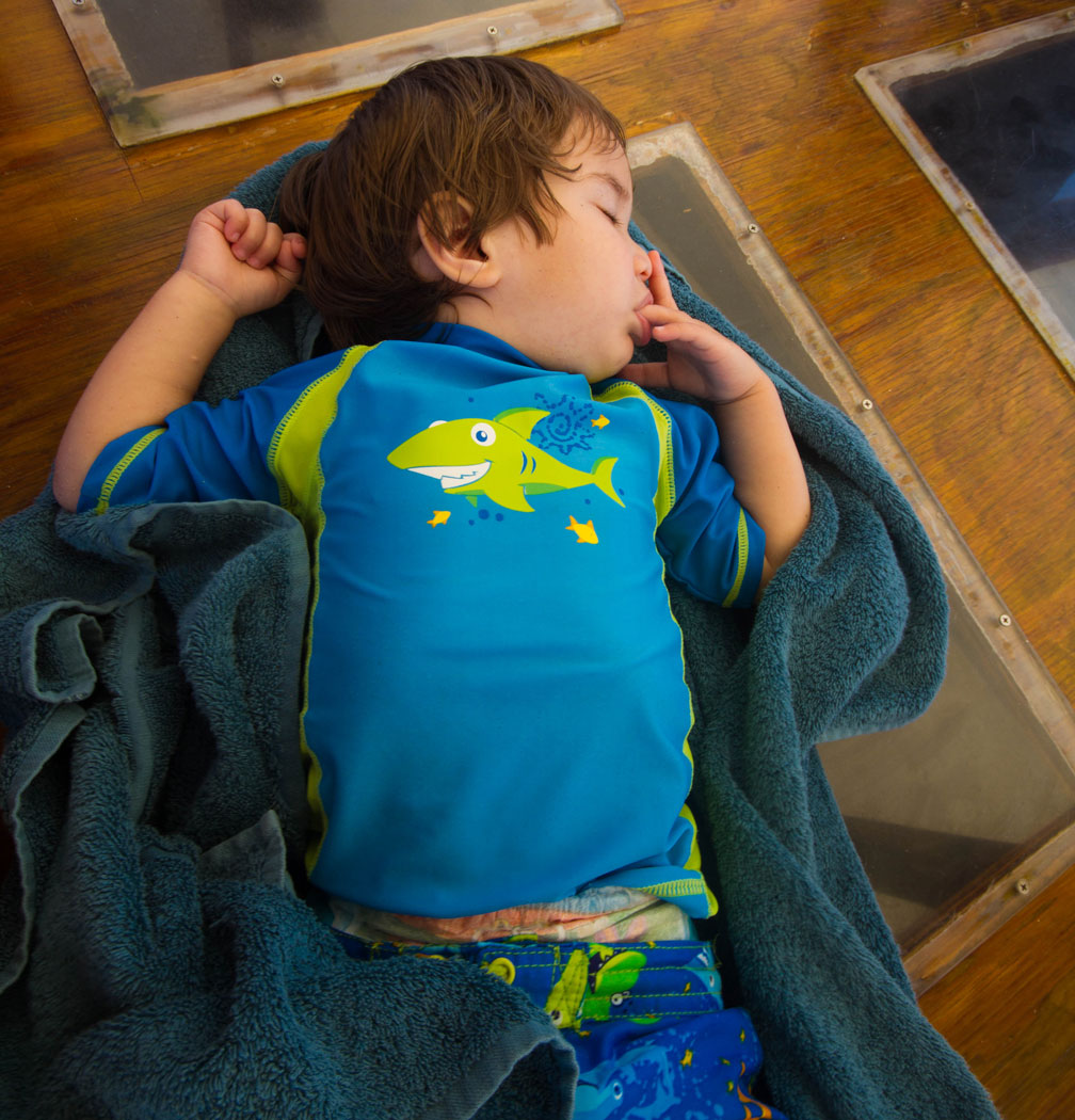 A toddler in swimwear naps on the deck of a sail boat in the Caribbean - Swimming with Turtles in the Tobago Cays