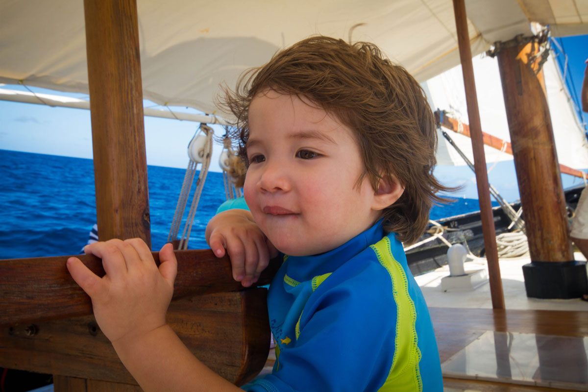 A young boy with wind blowing though his brown hair looks over the bow of a sail boat at sea - Swimming with turtles in the Tobago Cays