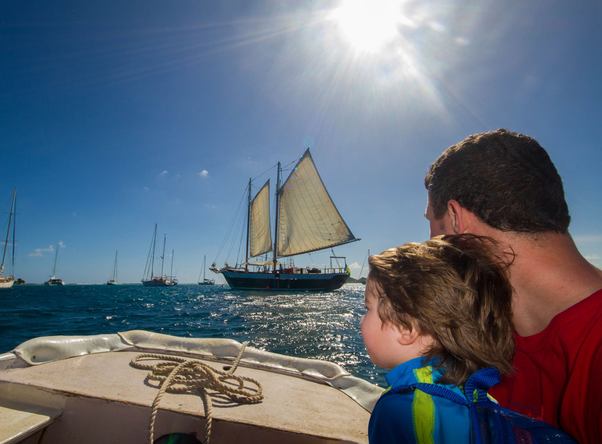 A father and young son look out from a boat towards a tall sail boat - Swimming with Turtles in the Tobago Cays