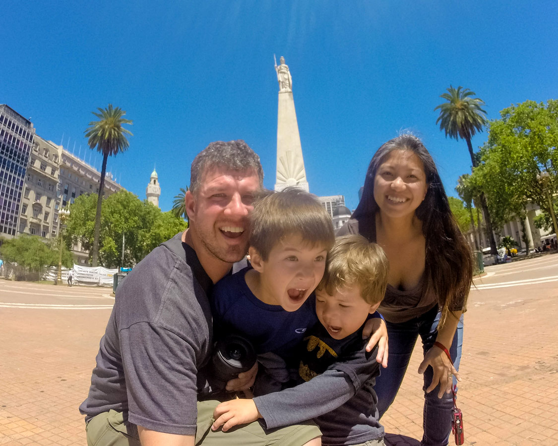 Family take a picture in front of the Pyramide de Mayo in microcentro which has many Buenos Aires highlights.