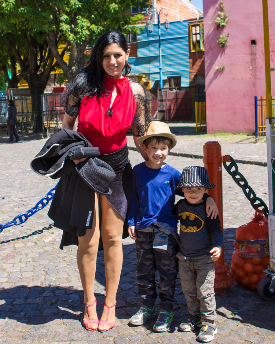 Two boys pose with a Tango performer in La Boca in Buenos Aires, Argentina.