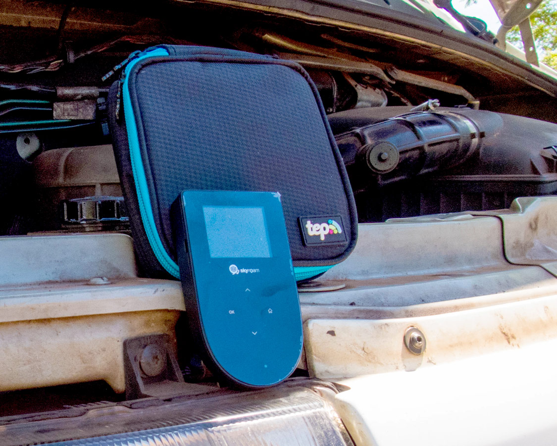 Small black digital Tep wifi hotspot device and carrying case sitting on the open hood of a van that has broken down.