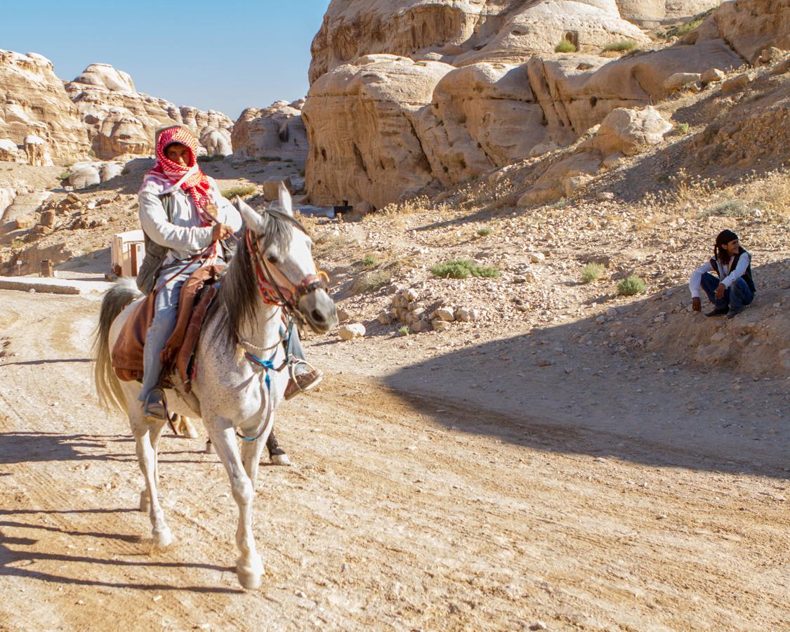 Petra for kids Bedouin horseman riding towards al Siq in Petra Jordan