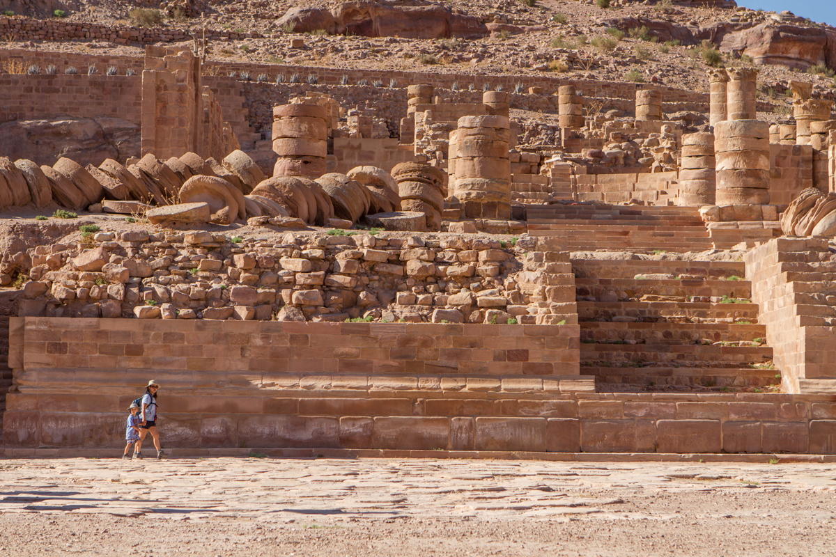 Family travel to Petra Jordan A mother and son walk along the walls of the Great Temple in Petra Jordan