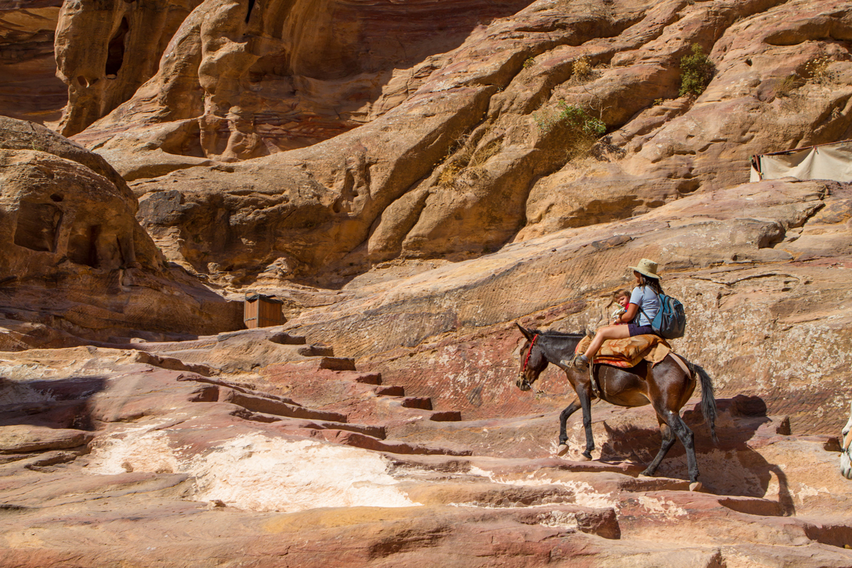 Petra Family Travel A mother and toddler ride a horse up the stairs to the Monastery