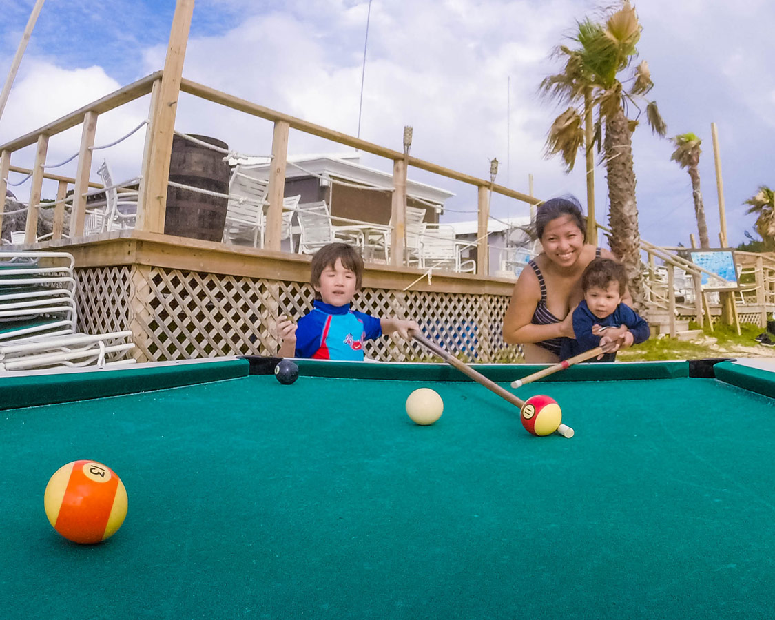 Woman and two boys playing outdoor billiards in Tobacco Bay, St. George Bermuda