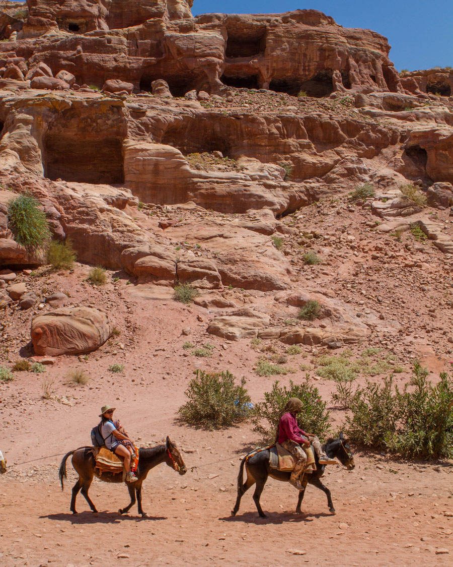 Petra for kids A Bedouin guide and a woman on horseback ride past cave houses in Petra Jordan