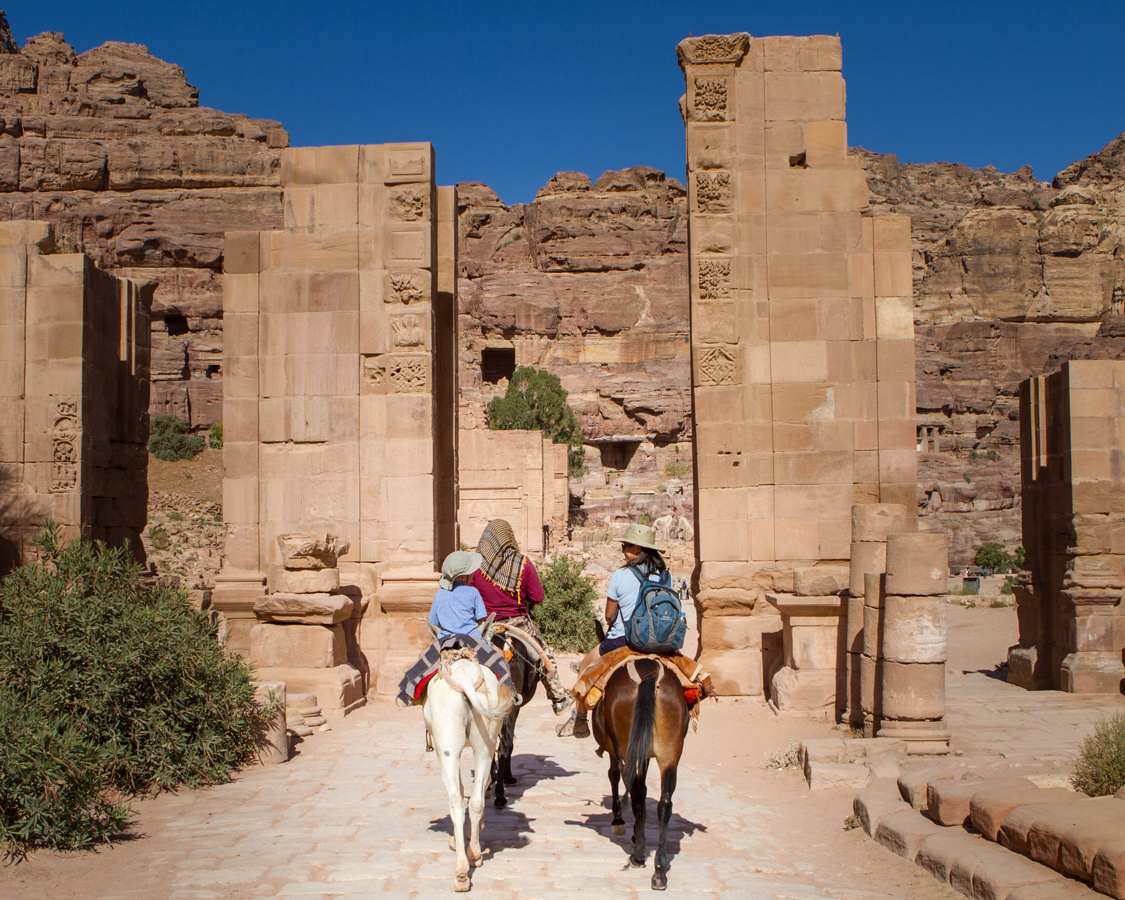 Petra for families A Bedouin guides a mother and two young boys on horseback through the Tremenos Gateway in on the way to the Monastery