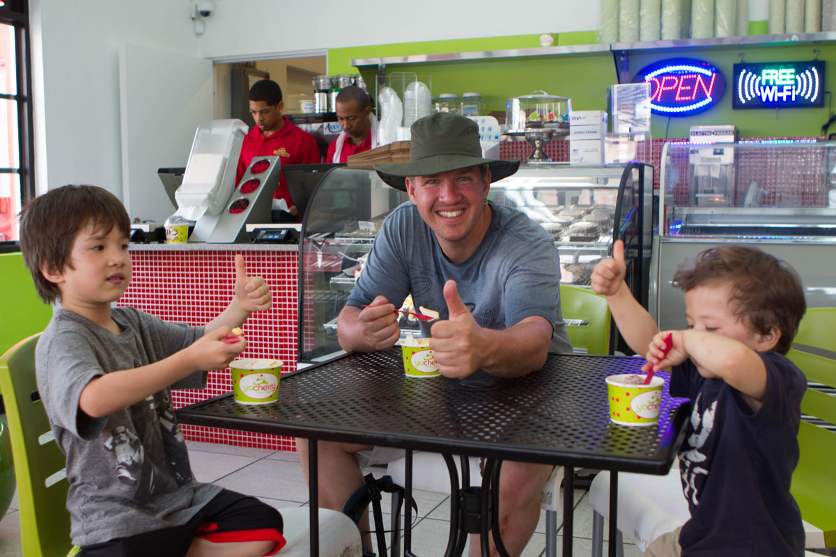Man with two boys sitting down and having frozen yogurt in St. George Bermuda