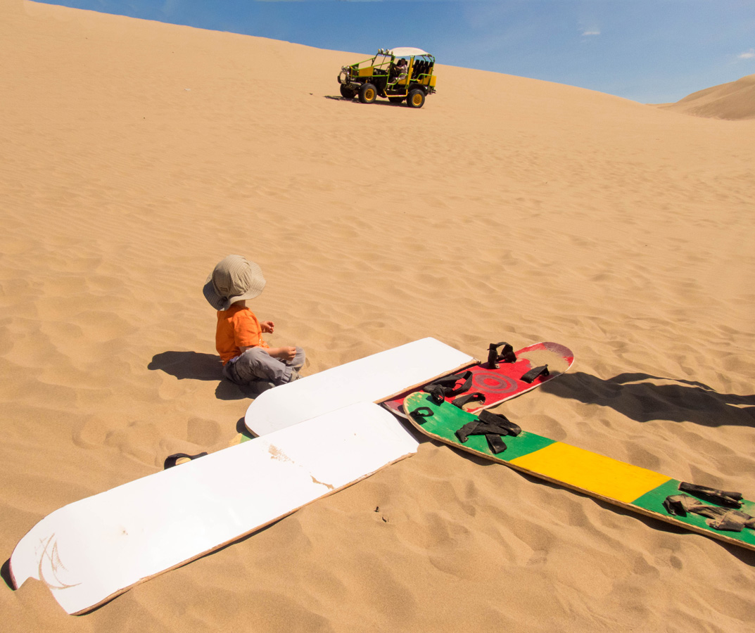 A toddler sits with sandboards in Peru while waiting for a dune buggy to pick him up