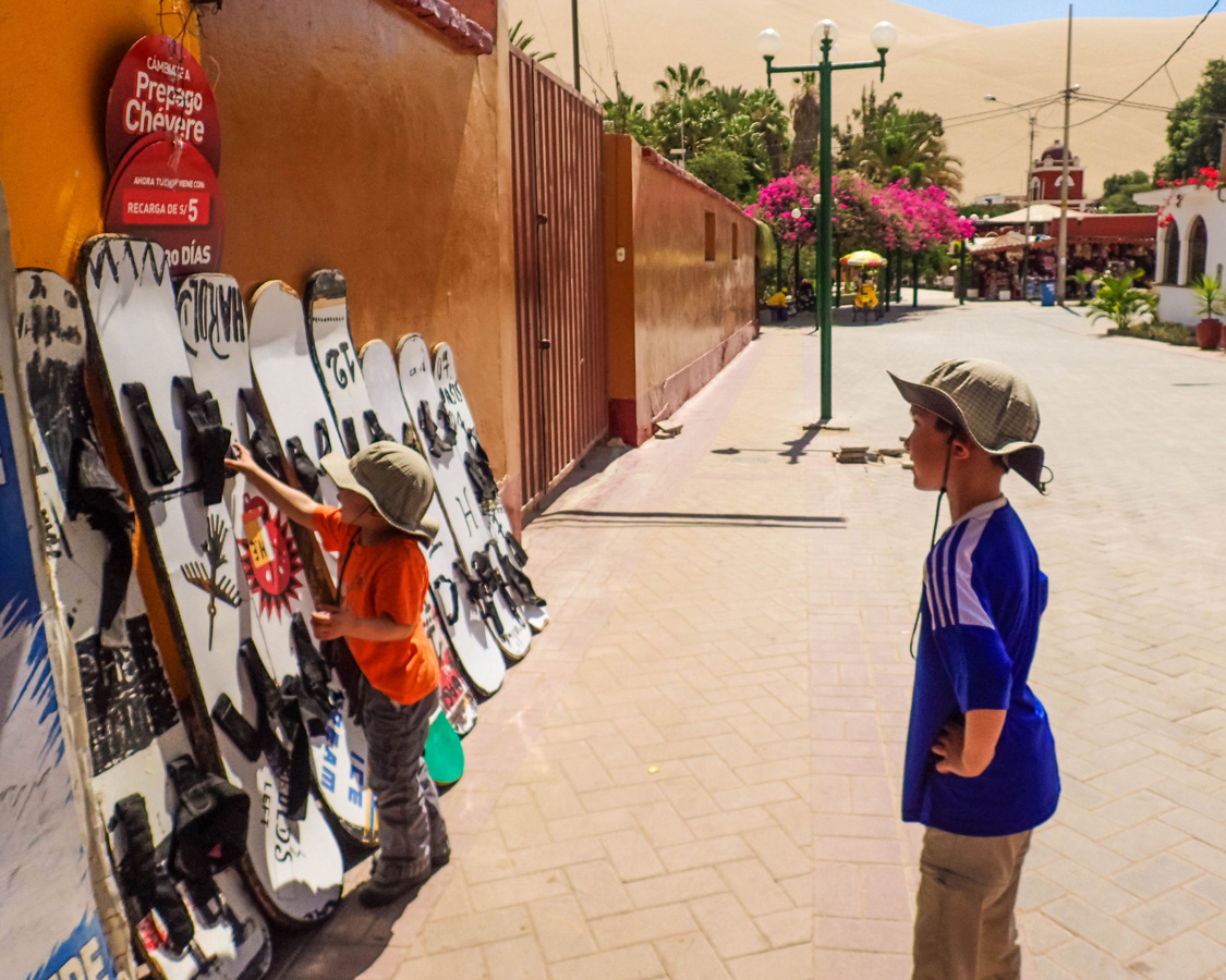 Young boy looks at sandboards on a street as he prepares to Sandboard in Huacachina Peru with Kids