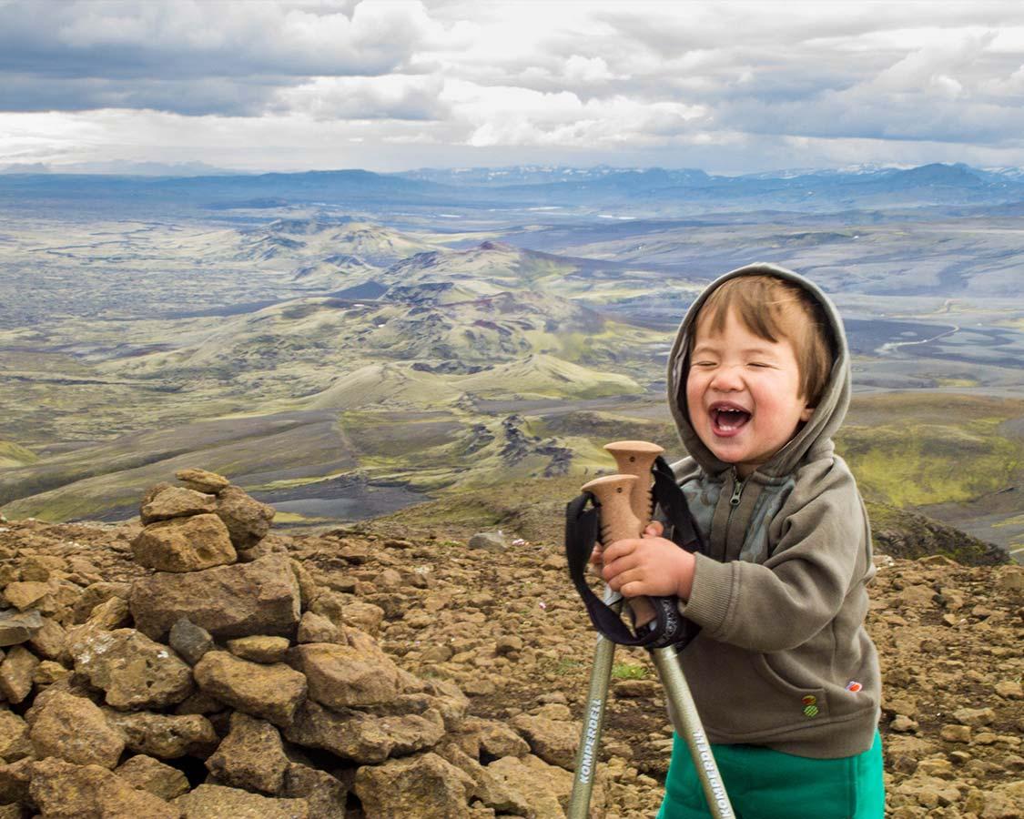Young boy laughing during trek Iceland at Lakagigar Crater Row