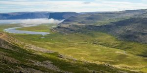 A valley lit by the sun among mountains in Iceland's Westfjords
