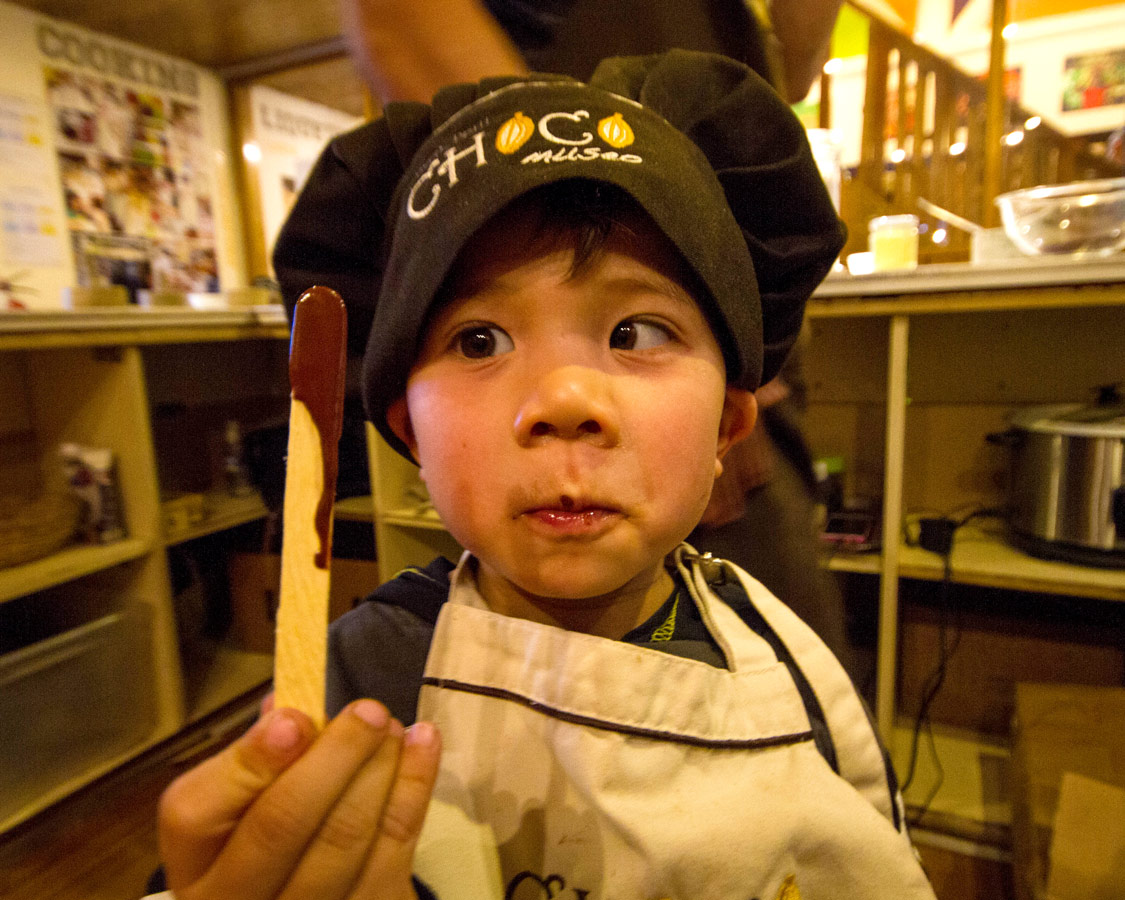 A toddler holds a stick of melted chocolate that he made at the ChocoMuseo in Cusco Peru