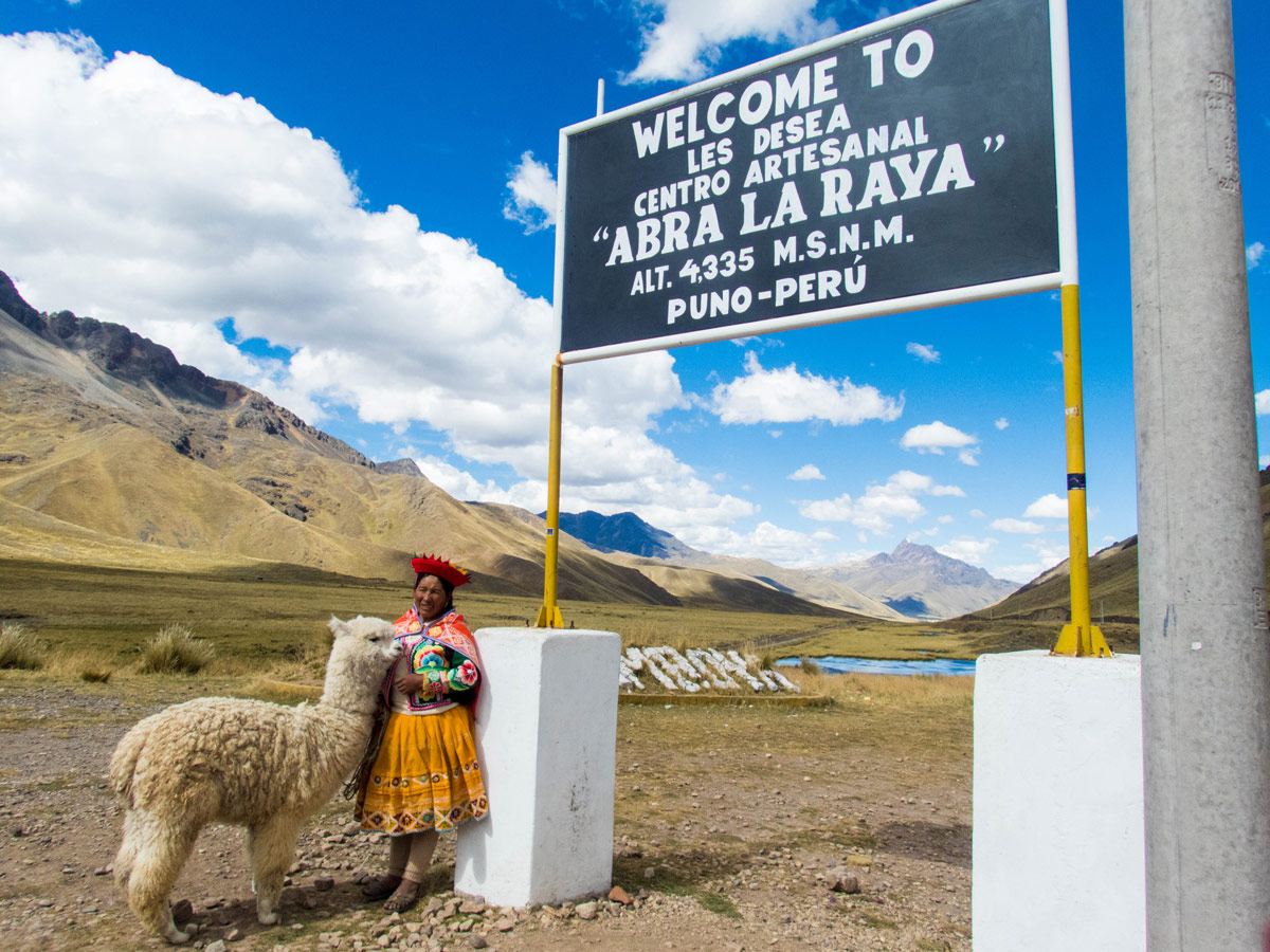A Peruvian Quechua woman stands with a llama next to a sign in La Raya Peru on the Cusco to Puno bus tour