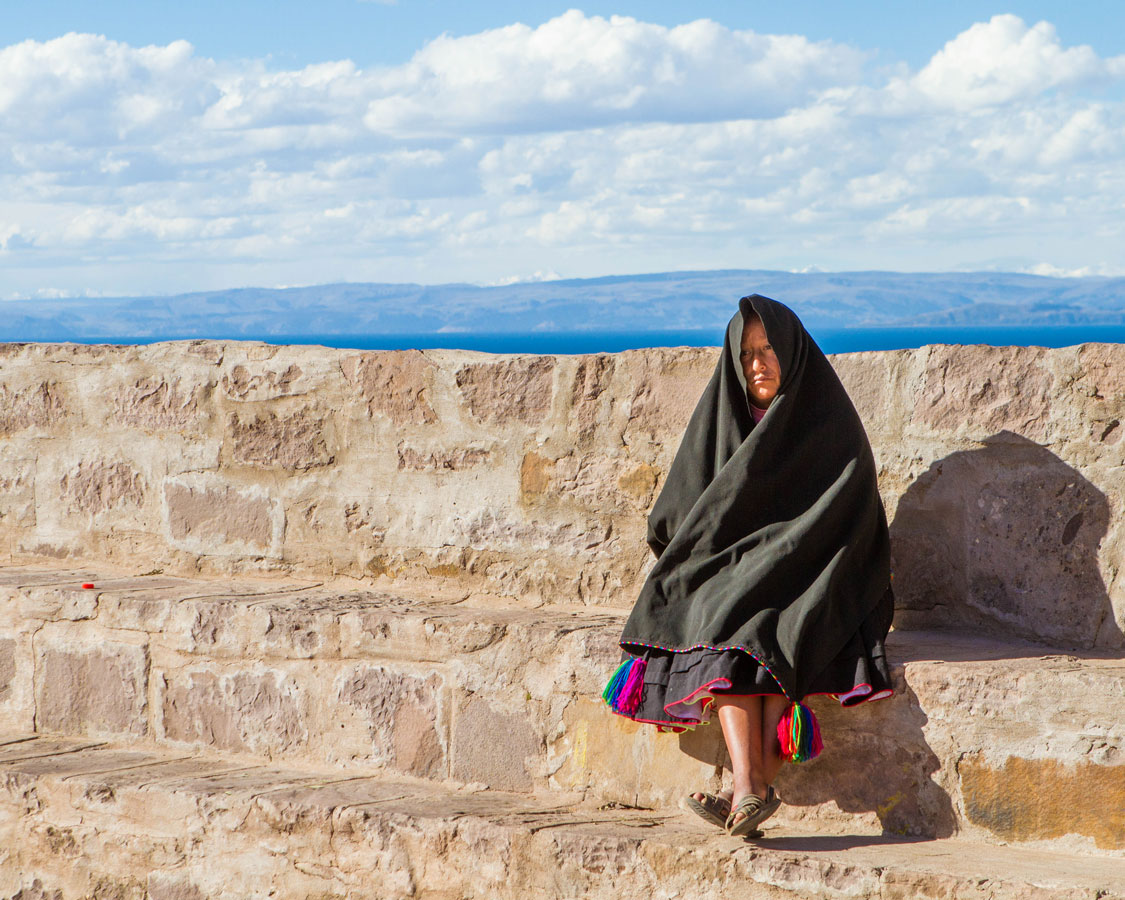 A Taquilenos woman in traditrional clothing sits on a stone wall on Taquile island on Lake Titicaca Peru