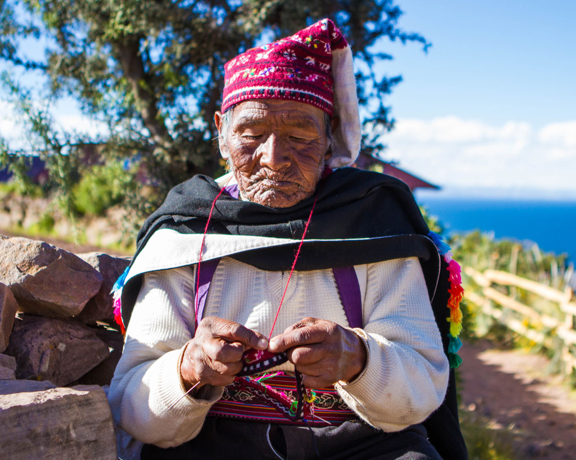 An elderly Taquileno man knits a hat on Isla Taquile on Lake Titicaca Peru